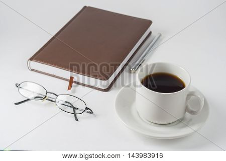 A Cup Of Coffee With Notepad On A White Table.