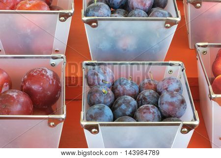 many baskets of plums on red background