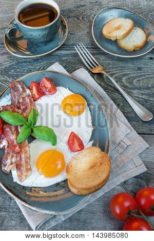Breakfast consists of fried eggs bacon tomato toast and a cup of coffee on the old wooden table