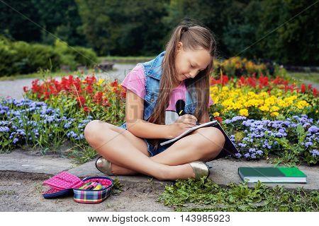 schoolgirl drawing in a notebook in the schoolyard