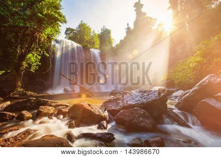 Tropical waterfall with sun rays in Cambodia. Lens flare and light leak