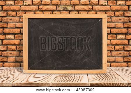 Blank blackboard on diagonal wooden table at red brick wall Template mock up for adding your design and text.