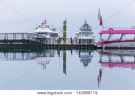 Couple of tour boats waiting quietly for tourists an early morning on a cloudy rainny day at Sun Moon Lake Taiwan