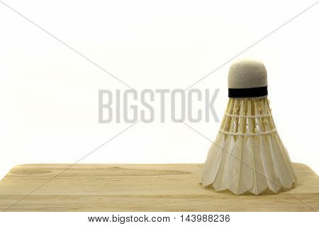 Badminton shuttlecock on wooden and white background.