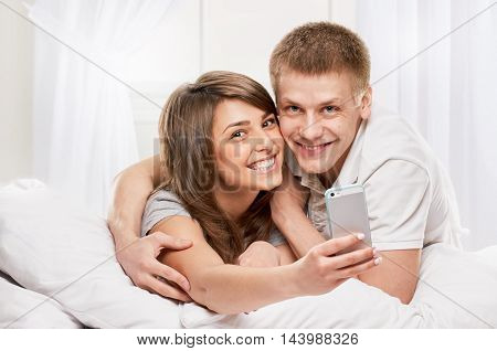 Happy smiling couple laying laughing in bed on light window background