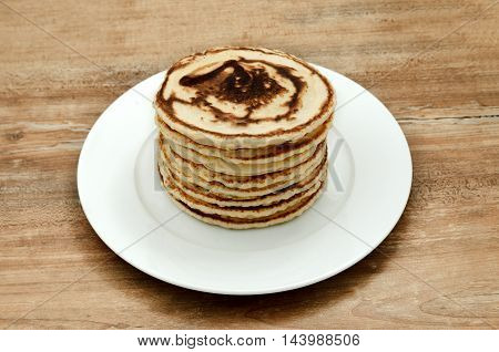 Big stack of a golden pancakes at a plate.