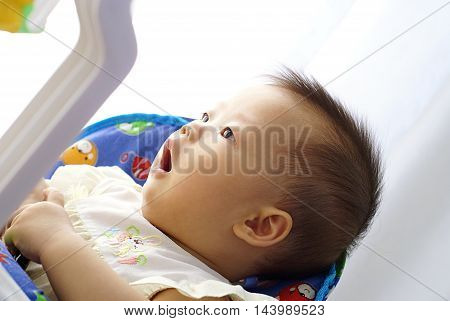 Cute Asian infant baby playing in baby walker, She expressed surprise with something.