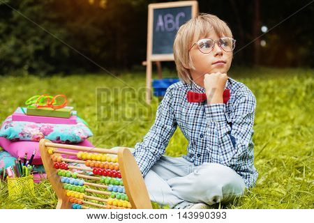 stylish little boy sits and thinks. The concept of training and education.