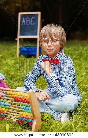 stylish little boy teaching mathematics. The concept of training and education.