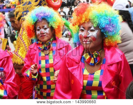 Cajamarca Peru - February 7 2016: Close up of two women in colorful clown costumes marching in Carnival parade in Cajamarca Peru on February 7 2016