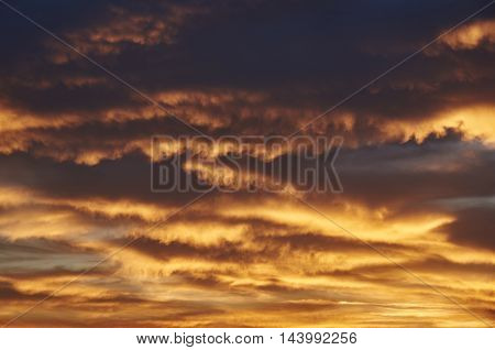 Rain cumulus clouds sundown. Clouds of orange and golden. Background
