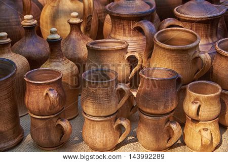 Ceramic tableware handmade clay in natural sunlight: cups bottles jars