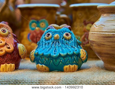 Blue owl - pottery handmade from clay glazed in natural sunlight against a background of other ceramic products