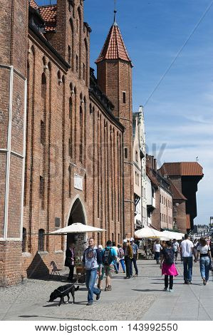 GDANSK POLAND - JUNE 15: many people walk by sunny street located in old city in Gdansk Poland on June 15 2016.