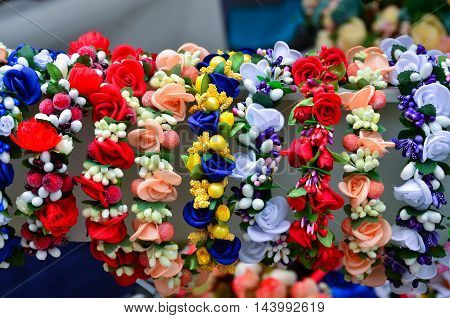 A very colorful floral headband selling on market stall.