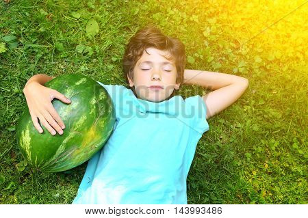 preteen handsome boy with water melon close up portrait on the summer sunny green grass background