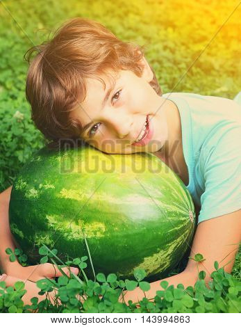 laughing preteen handsome boy with water melon close up portrait on the summer sunny green grass background