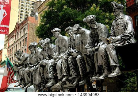 New York City - August 22 2004: Sculpture of iron workers having lunch sitting on a beam during the 1932 construction of Rockefeller Center displayed on West Broadway in Soho