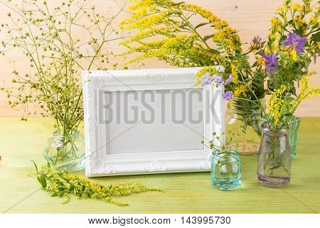Craft mockup set with Yellow wildflowers and white photo frame on a light wooden table