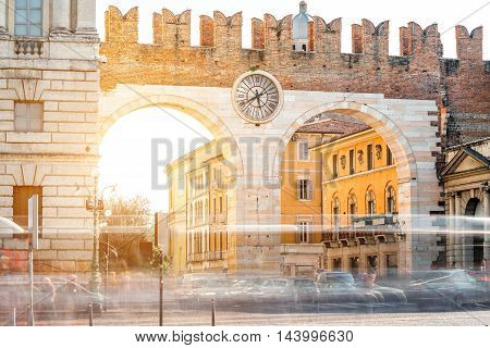 Portoni della Bra gate with clock in Verona city. Long exposure image technic with blurred cars and people