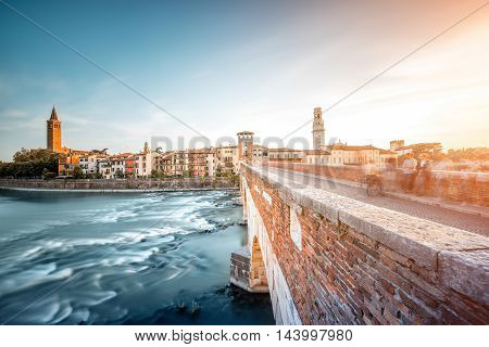 Verona cityscape view on the riverside with historical buildings and Stone bridge on the sunset