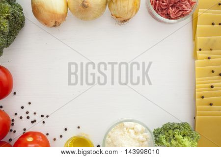 Set of ingredients for traditional italian lasagna. white food background with free space for text. Pasta, tomatoes, fresh ground meat, parmesan, onion, broccoli.