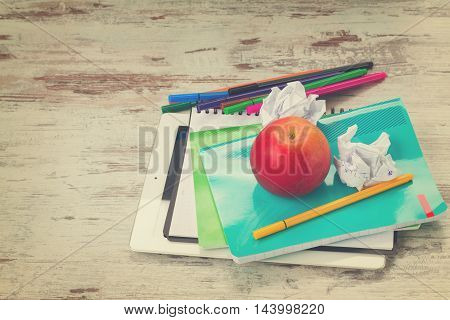 Apple with school supplies on aged white wooden table, retro toned