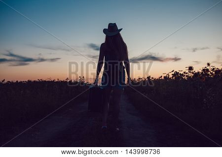 Girl in a cowboy hat standing with a suitcase on the road in the sunflower field. Waiting for help. Sunset.