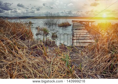 Old wooden pier with dry reed on sunset. Cloudy weather