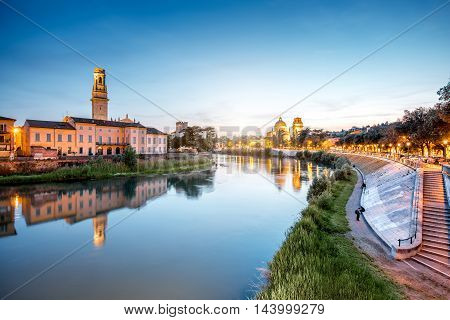 View on Adige river with Verona cathedral and saint George church at the evening in Verona city in Italy