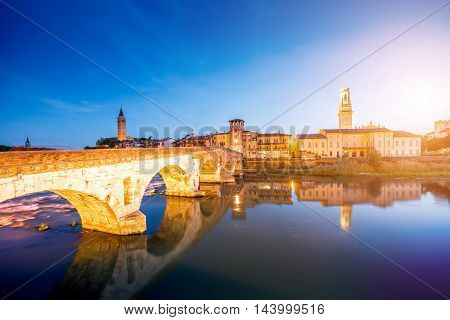 Verona cityscape view on the illuminated riverside with historical buildings and towers on the sunset