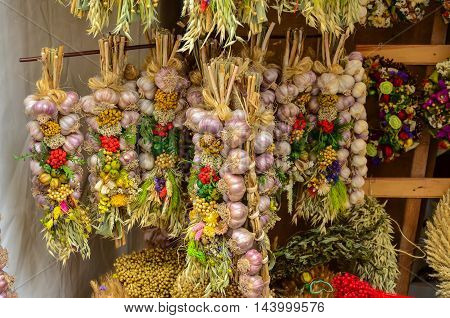 Decorative and fresh garlic bulbs hanging from market stall