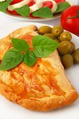Calzone with olives, caprese salad and fresh basil