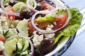 Close-up of bowl of Greek salad.  Luscious vine-ripened tomatoes, with feta cheese, kalamata olives,