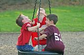 stock photo of tire swing  - Three boys having a blast playing on a tire swing