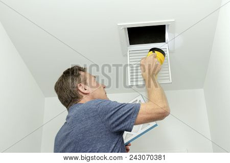 Man Inspecting Air Ducts Shining