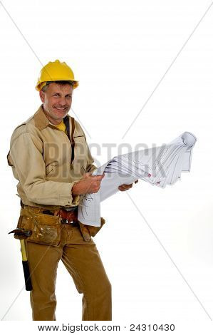 Male Construction Worker In A Hardhat And Tool Belt Holding Blue Prints.
