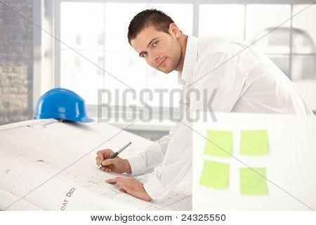 Schöner junger Ingenieur zeichnen Pläne in hellen Büro.?
