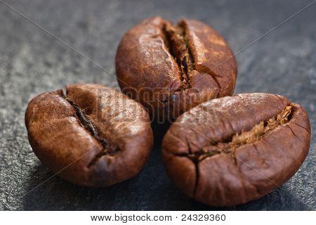 three coffeebeans on black stone