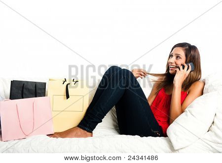 Beautiful happy asian teenage girl lying on the sofa, with shopping bags, listening on the phone and playing with hair