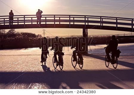 Biking on ice in the countryside from the Netherlands at sunset
