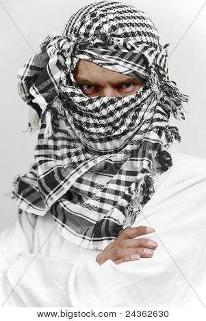 Arab muslin in white cloth and kaffiyeh shemagh head gear with stern threatening look