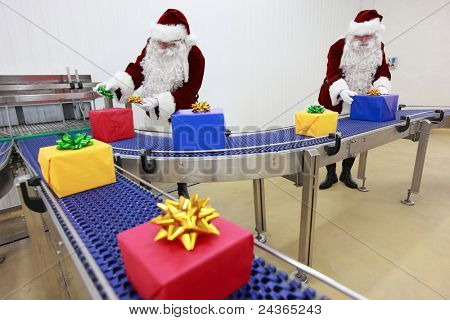 Two santa clauses working at production line - manufacturing gifts in boxes,ornamenting them.