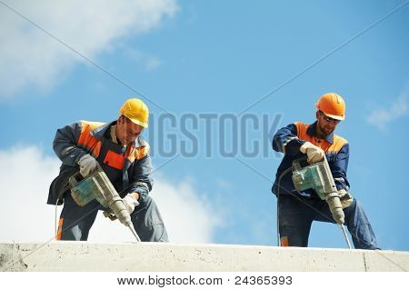 Two Builder workers with pneumatic hammer drill equipment at construction site