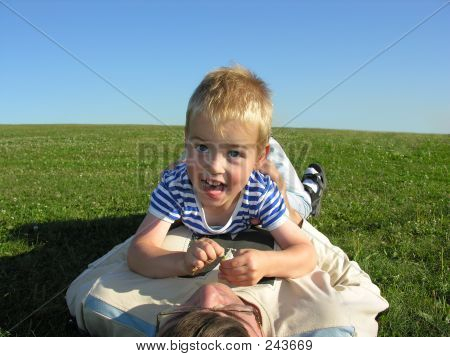 Son Lie On Father On Green Grass