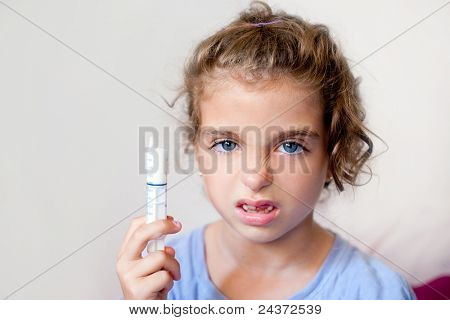 Unhappy kid girl with syringe medicine dose funny expression