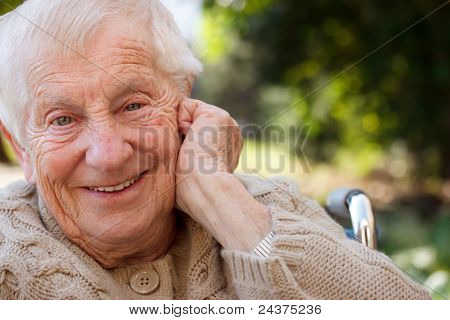 Happy senior lady in wheelchair smiling