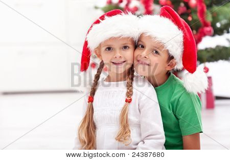 Children at christmas time in front of the fir tree wearing santa hats
