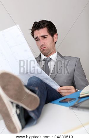 Stressless businessman looking at construction plan