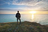 Man stands on the edge of the abyss and looks at the sea. Man relax on nature.  poster